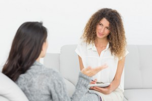 Therapist listening to her talking patient at therapy session